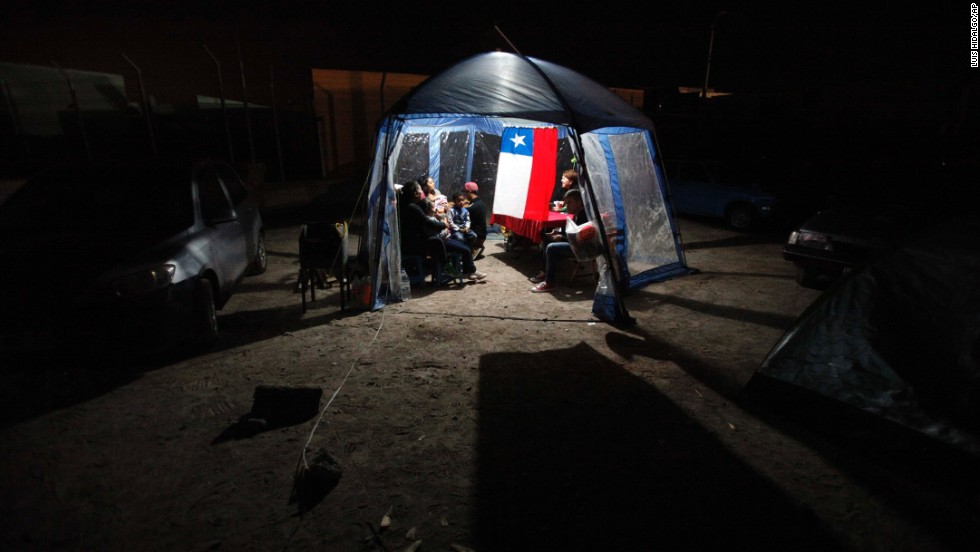 People take shelter under a tent after they left their homes in Alto Hospicio, Chile, on April 3.
