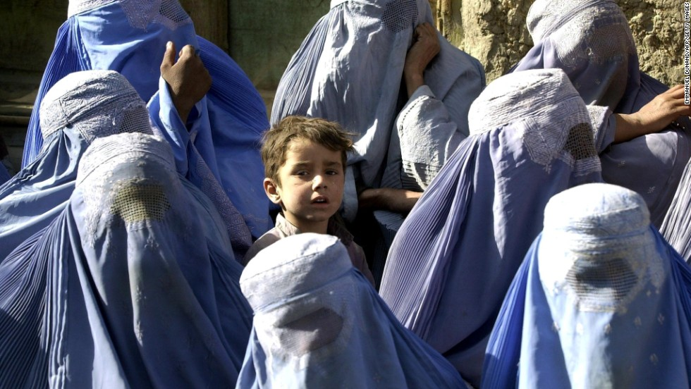 "A young boy stands among a group of veiled women waiting to receive food aid during a U.N. World Food Program distribution in Kabul in November 2001. ""I myself remember the mujahideen's takeover of Kabul on 27 April 1992,"" says Mosadiq. ""On 26 April I wore a miniskirt and a sleeveless shirt, but the day after I was terrified to walk outside without being fully covered."""