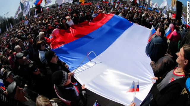 "Pro-Russian activists hold a huge Russian national flag in front of the regional administration building in Donetsk, Ukraine, Sunday, April 6, 2014. In Donetsk a large group of people surged into the provincial government building and smashed windows. A gathering of several hundred, many of them waving Russian flags, then listened to speeches delivered from a balcony emblazoned with a banner reading a ""Donetsk Republic"". (AP Photo/Andrey Basevich)"