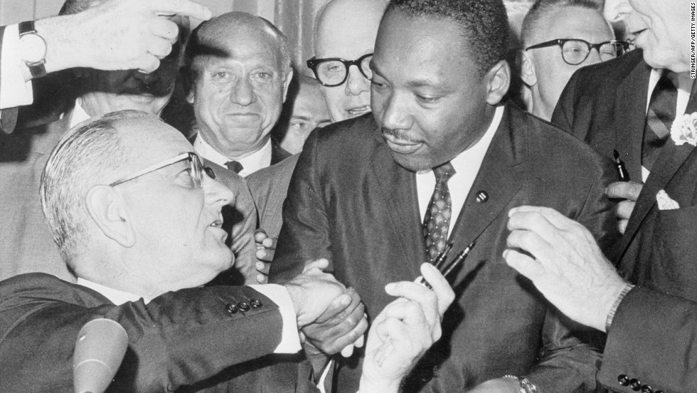 "After signing <a href=""http://www.cnn.com/2014/04/10/politics/civil-rights-act-interesting-facts/"">the Civil Rights Act of 1964</a>, U.S. President Lyndon B. Johnson shakes hands with the Rev. Martin Luther King Jr. The legislation outlawed discrimination in public places and banned discrimination based on race, gender, religion or national origin. It also encouraged the desegregation of public schools."