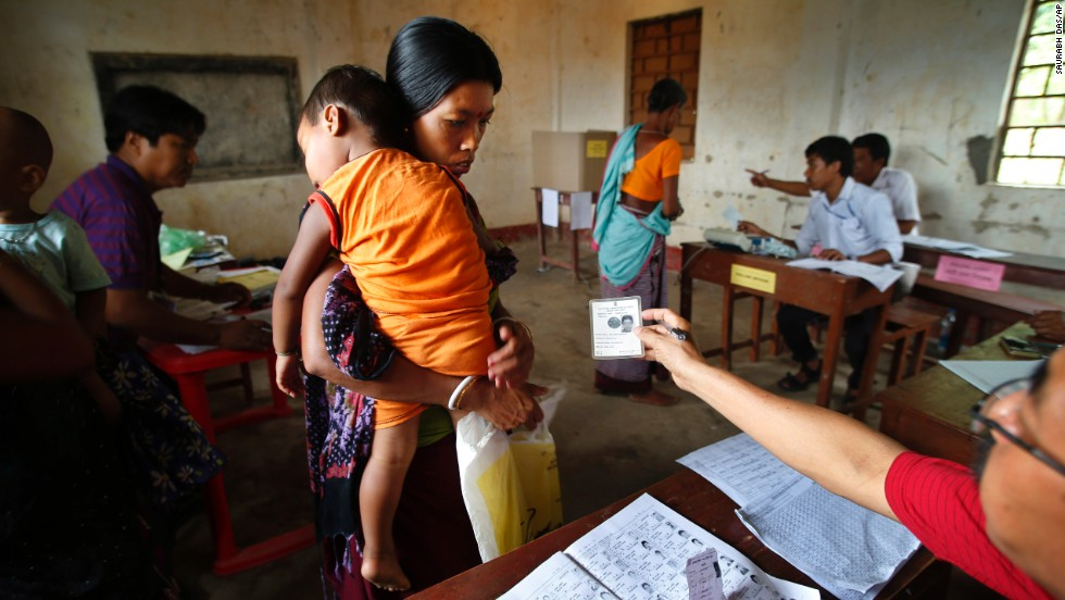 An official checks a voter's identity card in Agartala, India, on Monday, April 7.