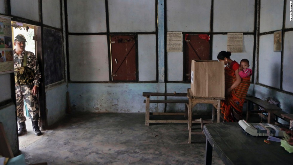 A woman with a baby casts her vote inside a polling center at Misamora Sapori, an island in the Brahmaputra River, on April 7.