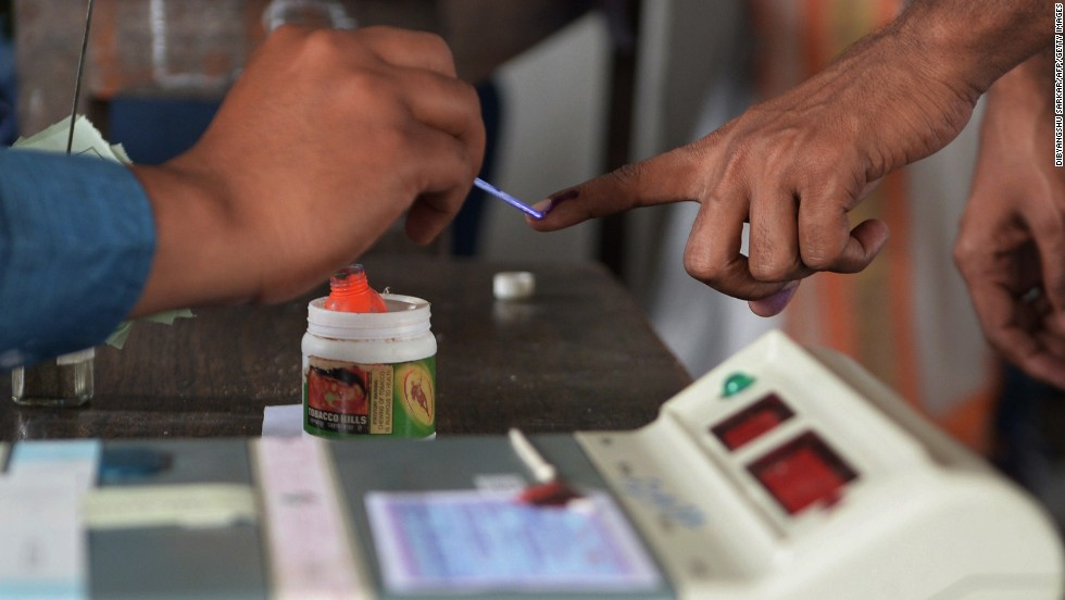 An election officer uses ink to mark a voter's finger at a polling station in Dibrugarh on April 7.