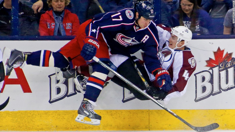 Columbus' Brandon Dubinsky, left, checks Colorado's Tyson Barrie while chasing the puck during an NHL game Tuesday, April 1, in Columbus, Ohio.