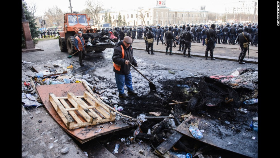 Workers clean up on April 8 after pro-Russian separatists and police clashed overnight in Kharkiv.