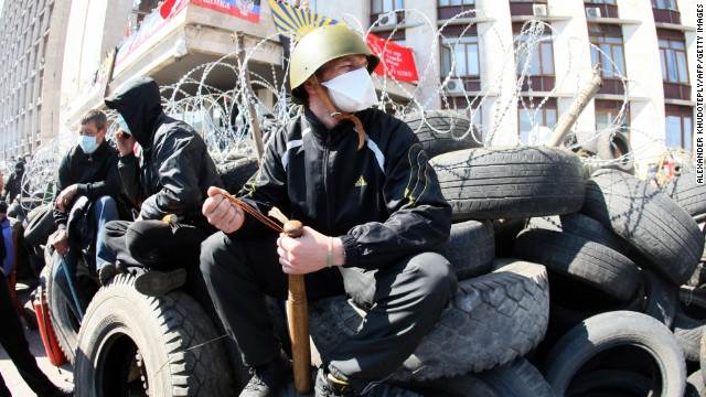 "A pro-Russian militant holding a bat guards a barricade in front of the Donetsk regional administration building on April 8, 2014. Ukraine mounted a counteroffensive on April 8 by vowing to treat the separatists as ""terrorists"" and making 70 arrests in a nighttime security sweep, while hundreds of militants remained holed inside the Donetsk administration building a day after proclaiming the creation of an independent ""people's republic"" and demanding that an independence referendum be held before May 11."