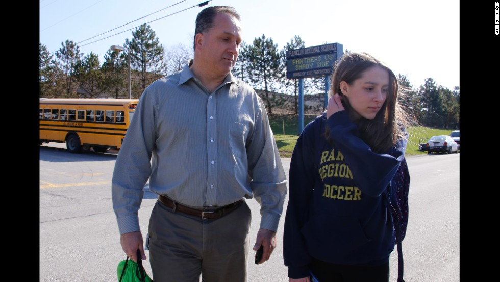 Jenna Mickel, a sophomore at Franklin Regional High School, stands with her father, Richard, as she talks to reporters outside the school on April 9.