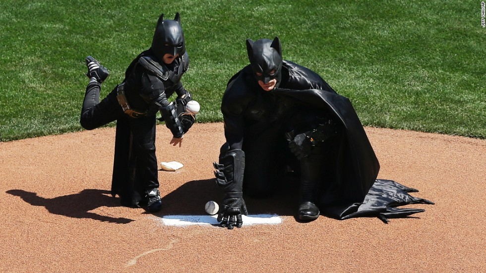 Miles throws the ceremonial first pitch next to Batman.