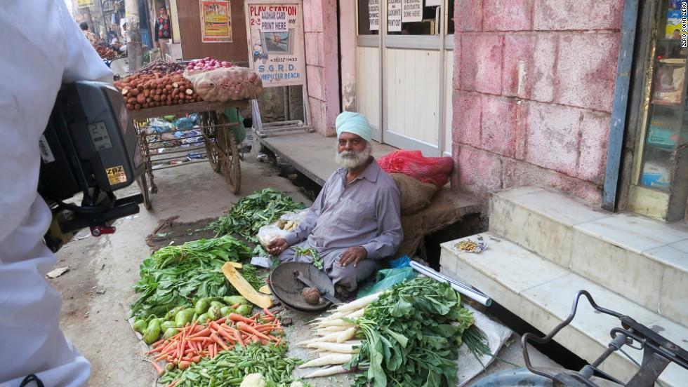 A produce vendor sits among his offerings on the packed streets of Amritsar.