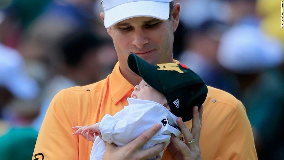 Kevin Streelman holds his baby girl, Sophie, before sampling the greens of Augusta.