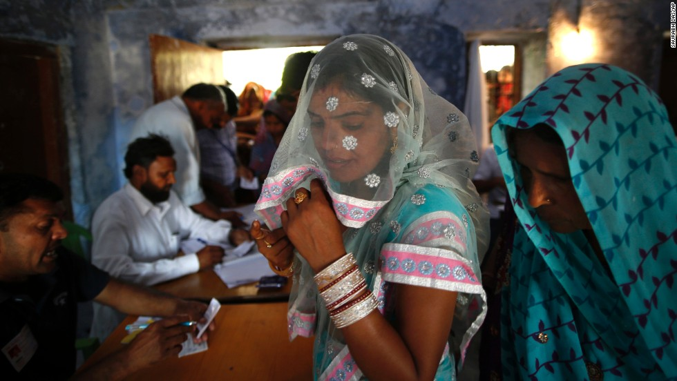 Voters wait for their identities to be verified before casting their ballots April 10 in Haryana, India.