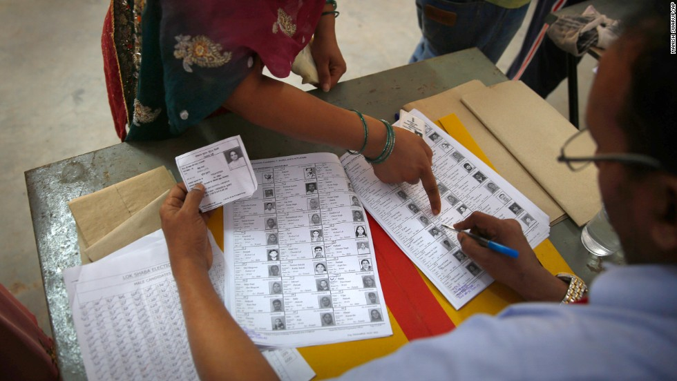 A woman points out her photo before casting her vote in New Delhi on April 10.