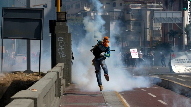 A masked anti-government demonstrator returns a teargas canister to Bolivarian National Guards during clashes in Caracas, Venezuela, Saturday, April 12.