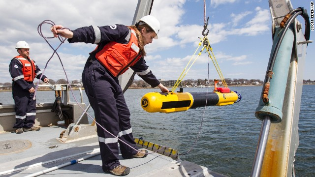 A submarine built by Bluefin Robotics is lowered into the water by systems engineer Cheryl Mierzwa in Quincy, Mass., Wednesday, April 9, 2014. Bluefin Robotics shipped a version of their submarine to help locate the missing Malaysian Airlines Flight 370, by using its side-scan sonar. (AP Photo/Scott Eisen)
