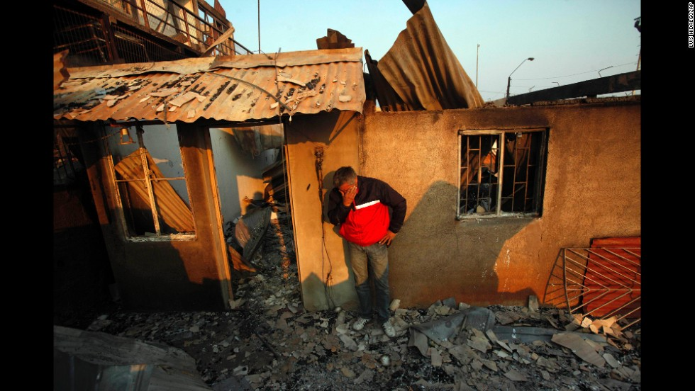 A man cries next to the remains of his house in Valparaiso.