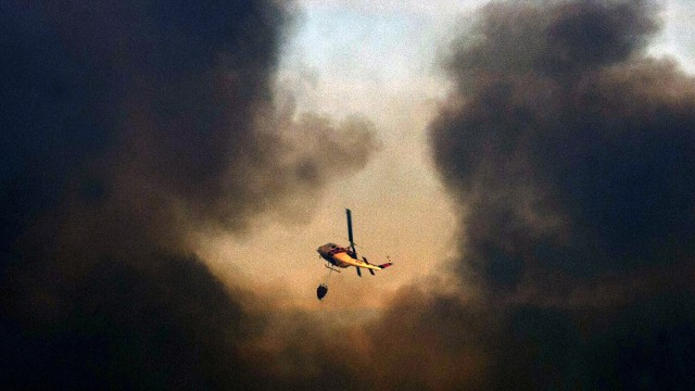 A helicopter flies over Valparaiso during efforts to quell the flames on April 13.