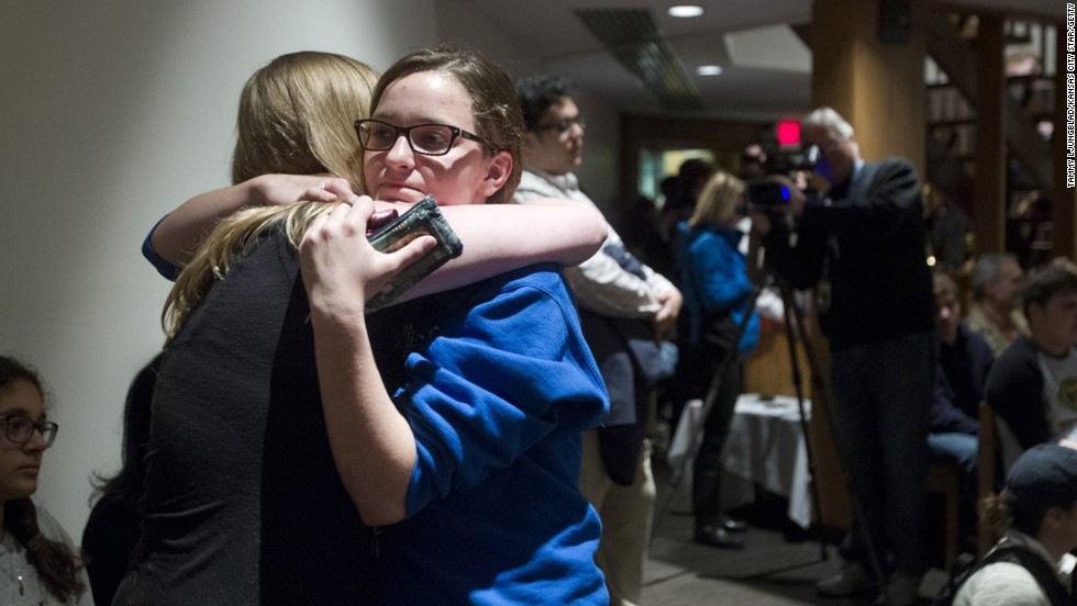 Rachel Trout, 16, receives a hug from a friend after addressing the crowd at St. Thomas the Apostle.