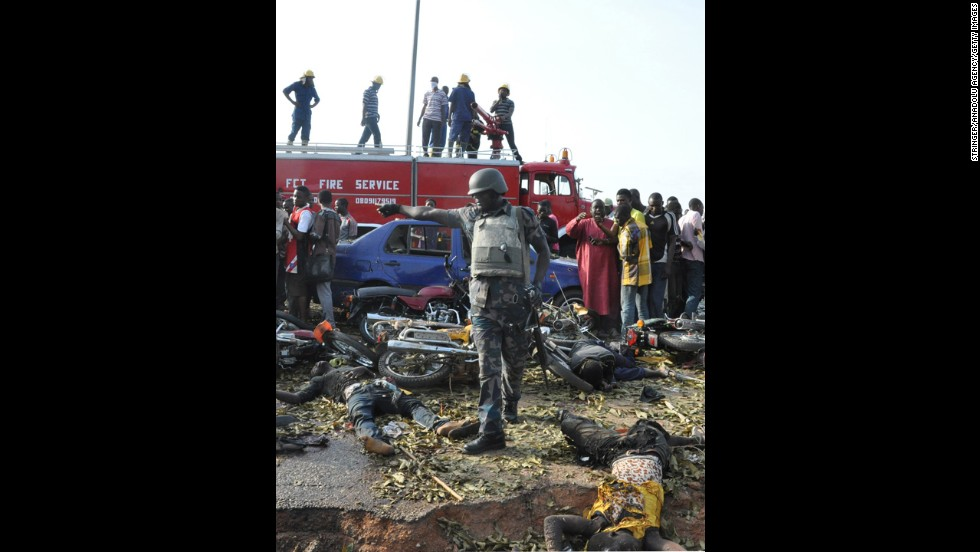 Nigerian security forces gather at the site of the blast April 14. The bus station was crowded with commuters when the explosion happened at about 6:45 a.m.