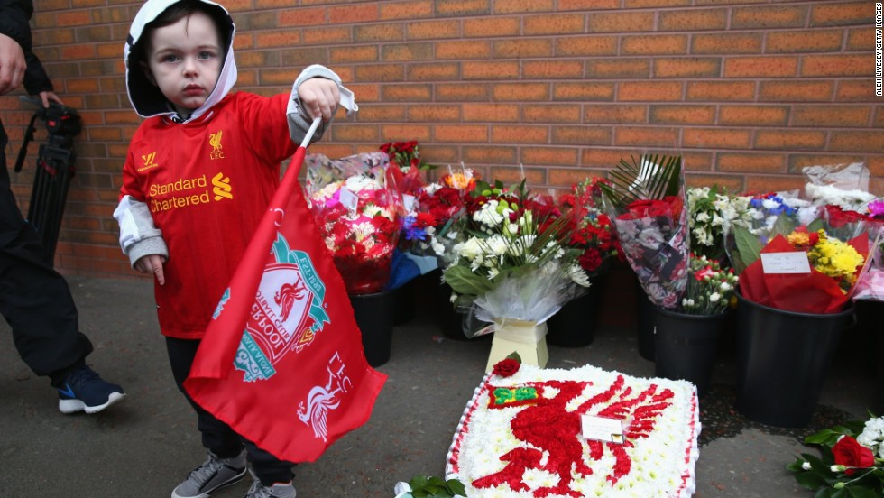 A young fan stands next to floral tributes laid in memory of the victims ahead of the Liverpool-Manchester City game at Anfield.