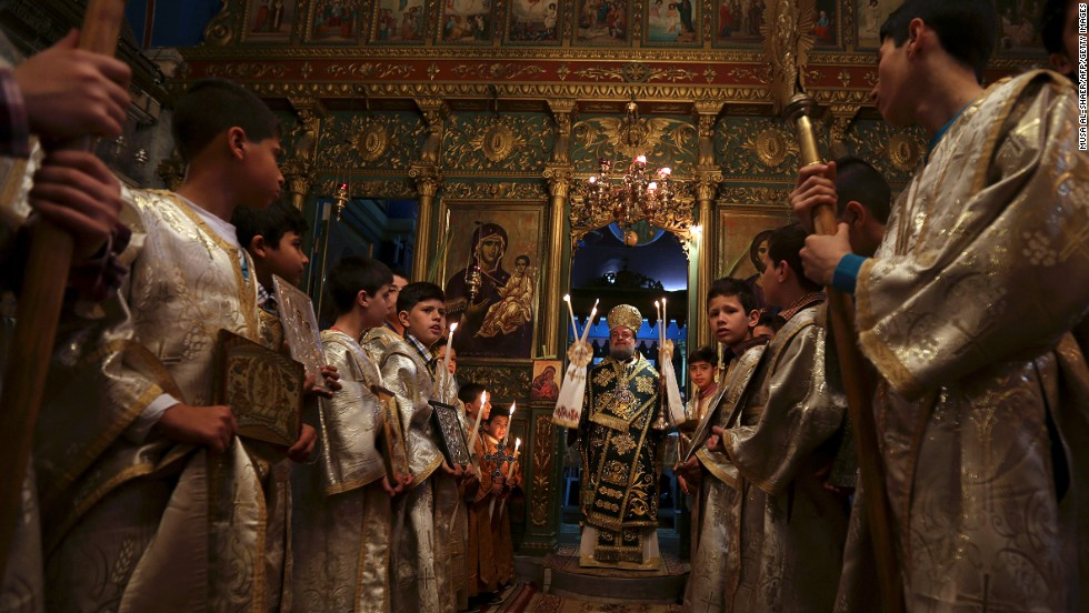 "BETHLEHEM, WEST BANK: The head of the Greek Orthodox church, Bishop Theofilactos, holds the Palm Sunday mass at the Church of the Nativity on April 13. <a href=""http://www.cnn.com/video/data/2.0/video/world/2014/04/14/jerusalem-palm-sunday.cnn.html"">CNN spoke to Christians celebrating in Syria and Palestine.</a>"