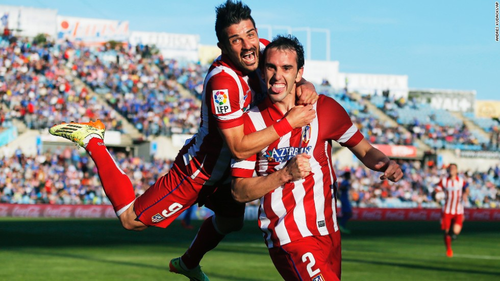 Atletico Madrid forward David Villa jumps on teammate Diego Godin after Godin's goal Sunday, April 13, in a Spanish league soccer game versus Getafe. Atletico won the game 2-0 to stay atop the league.
