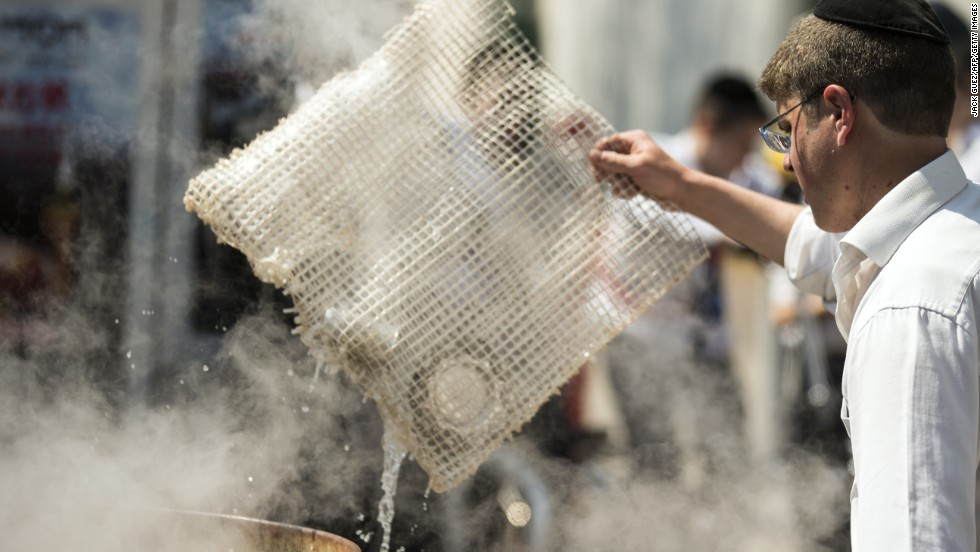 An Israeli man immerses cooking items into boiling water to make them kosher for Passover in Bnei Brak, near Tel Aviv, on April 14.