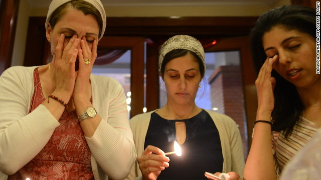 Israeli Jewish worshippers light candles as they perform a ceremony for Passover in Kathmandu on April 14, 2014. Hundreds of Jewish travellers in Kathmandu attended what organisers claim was the world's biggest Passover celebration, as food supplies delayed for weeks due to a diplomats' strike arrived just hours before the feast. AFP PHOTO / Prakash MATHEMA