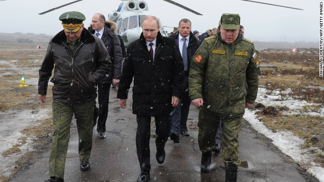 Russia's President Vladimir Putin (front C) and Defence Minister Sergei Shoigu (front L) walk to watch military exercises upon his arrival at the Kirillovsky firing ground in the Leningrad region, on March 3, 2014.