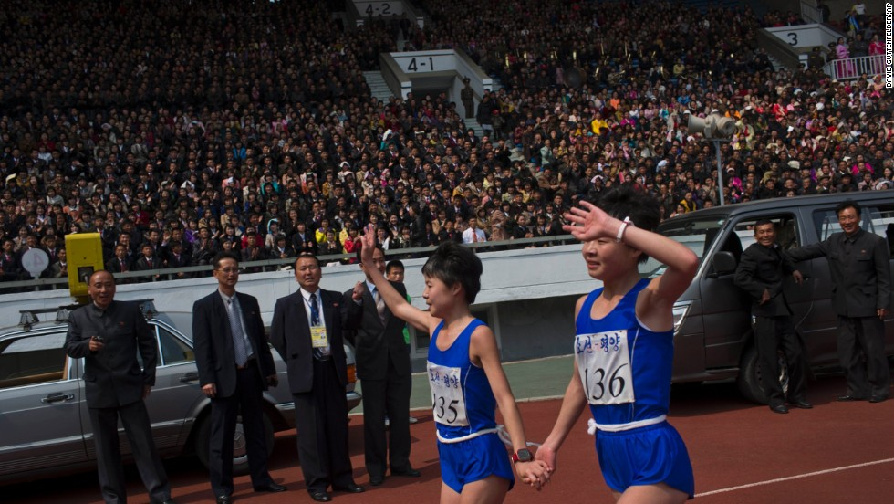 North Korean twin sisters Kim Hye Gyong (135) and Kim Hye Song (136) take a victory lap together after placing first and second respectively in the women's race.