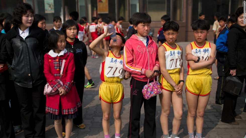 Young North Korean runners rest after finishing their part of the race.