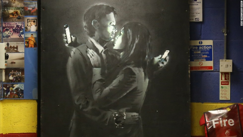 The artist has also taken on lighter themes: Banksy's Mobile Lovers, featuring a man and a woman embraced and looking at their mobile phones, sprayed onto a black wooden board is displayed inside the Broad Plain & Riverside Youth Project on April 16, 2014 in Bristol, England.