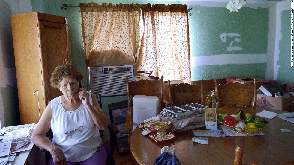 "Eleanor Castro sits in her home in West, Texas. Her property was damaged by the <a href=""http://www.cnn.com/2013/04/18/us/gallery/texas-explosion/index.html"">fertilizer plant explosion</a> a year ago that claimed 15 lives."