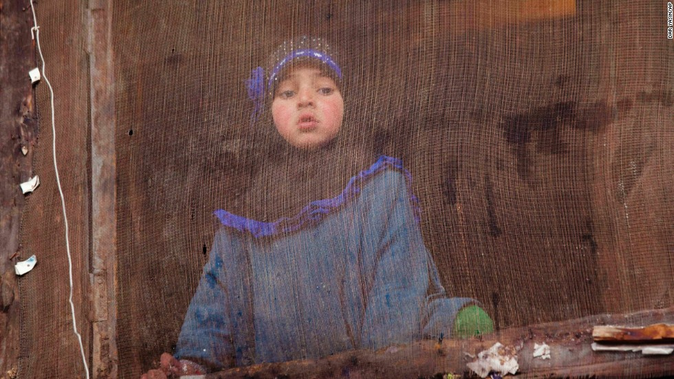 A young girl watches an election campaign rally from her house in Rawalpora, India, on April 15.