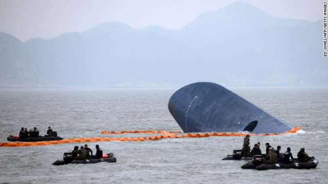 Coast guard members search for passengers near a South Korean ferry (C) that capsized on its way to Jeju island from Incheon, at sea some 20 kilometres off the island of Byungpoong in Jindo on April 17, 2014.  South Korean rescue teams, including elite navy SEAL divers, raced to find up to 293 people missing from a capsized ferry carrying 459 passengers and crew -- mostly high school students bound for a holiday island. AFP PHOTO   AFP PHOTO / ED JONES        (Photo credit should read ED JONES/AFP/Getty Images)