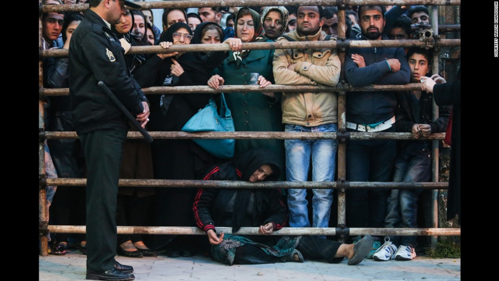 Koukab sits on the ground amongst the crowd before her son was brought out from the prison.