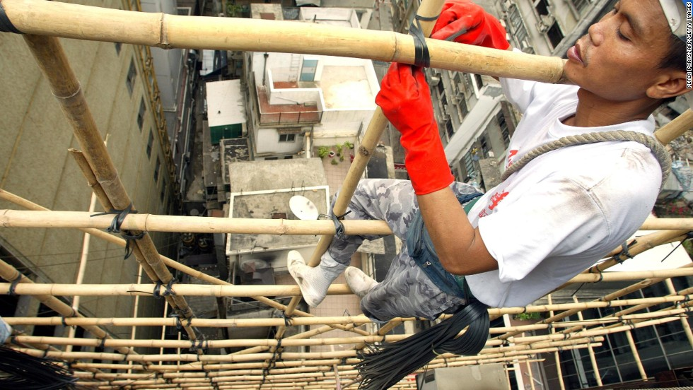 Bamboo scaffolders, perched precariously on bits of bamboo suspended in mid-air while attached to a small harness, are a common sight on Hong Kong's streets.