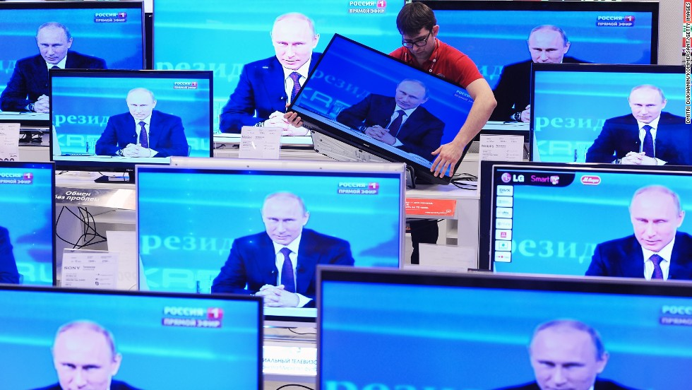 A shop assistant in Moscow moves a television screen Thursday, April 17, during the annual question-and-answer session held by Russian President Vladimir Putin.