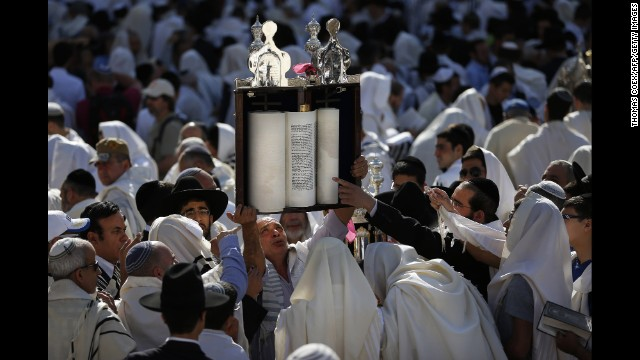 A man raises Torah scrolls during the Priestly Blessing at the Western Wall on April 17.