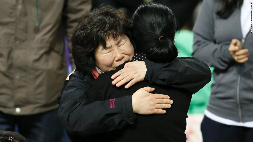 Family members of missing passengers hug as they await news of their missing relatives at Jindo Gymnasium on April 19.