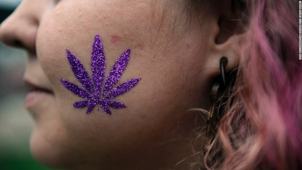 A glittery pot leaf adorns the cheek of an attendee in Denver on April 19.