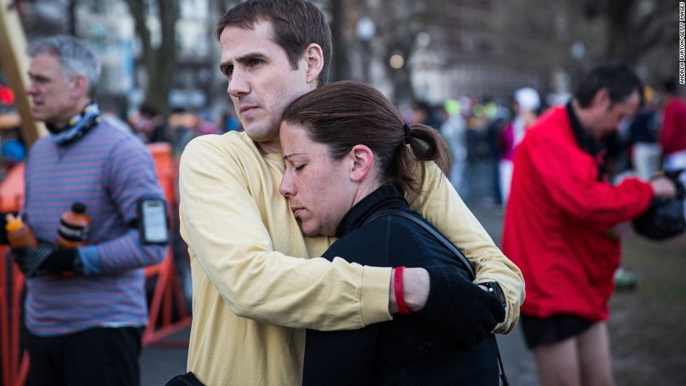 A couple waits for a bus to take them to the starting line on April 21.
