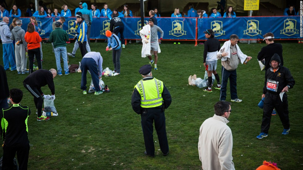 A police officer stands among runners preparing for the marathon on Boston Common.