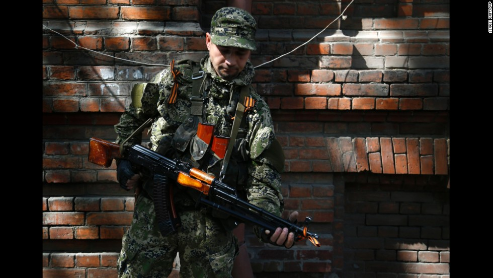 An armed pro-Russian man stands on a street in Slovyansk on Monday, April 21.