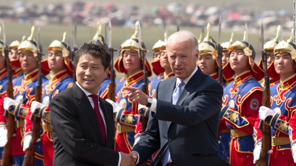 Biden shakes hands with Mongolian Prime Minister Sukhbaatar Batbold as they inspect honor guards after Biden's arrival at the Chinggis Khaan International Airport in Ulan Bator on August 22, 2011.