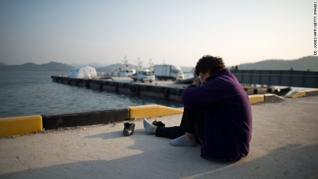 A relative weeps as she sits before the sea at an area where family members of victims of the South Korean ferry 'Sewol' are gathered, at Jindo harbour on April 21, 2014.
