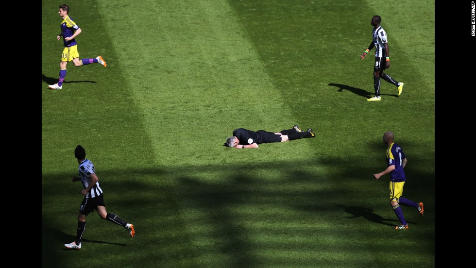 Referee Chris Foy, center, lies on the ground after being struck in the face by a reflected ball during the English Premier League soccer match between Newcastle United and Swansea City in Newcastle, England, on April 19.