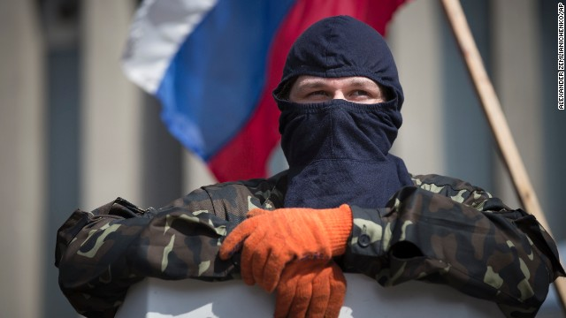 A masked pro-Russia guards barricades as the Russian national flag flies at the Ukrainian regional office of the Security Service in Luhansk, Ukraine, Monday, April 21, 2014.