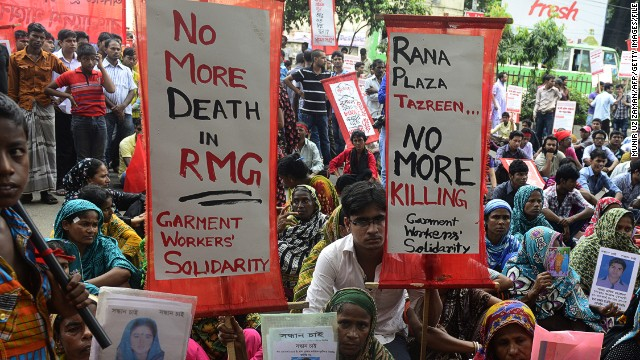 Mourners hold up portraits of their her missing relatives, presumed dead following the April 24 Rana Plaza garment building collapse in Bangladesh last year.