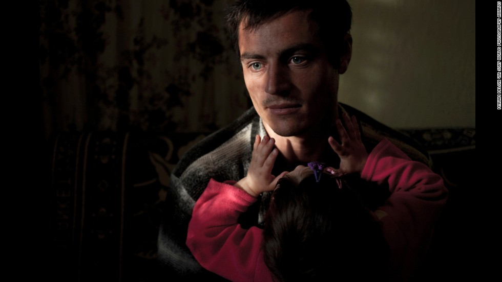 "Meloni said this image captures the helplessness of a young father who must care for his daughter alone while his wife lives and works in Russia. She says it portrays the difficulties of ""working and parenting in a country with serious economic problems and very few opportunities for personal development."""
