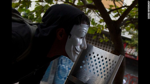 A masked protester watches clashes with the Bolivarian National Police in Caracas on Thursday, April 17.